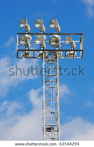 a football stadium floodlight with metal pole on blue sky - stock photo
