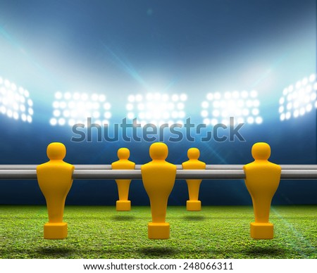 A football stadium with an unmarked green grass pitch and a row of yellow foosball players on it at night under illuminated floodlights - stock photo