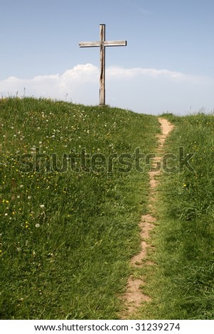 a footpath leads to a wooden cross on a hill