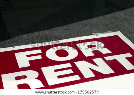 A For Rent Sign lies in a window of an empty window.