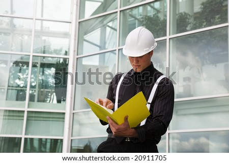 A foreman checks his blueprints outside of city hall.