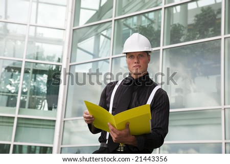 A foreman holding a folder outside of the office.