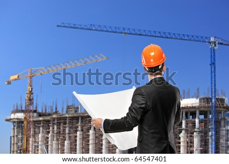 A foreman in a black suit holding a blueprints and looking towards the construction site - stock photo
