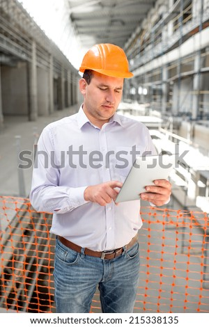 A foreman with digital tablet supervising the project at the construction.
