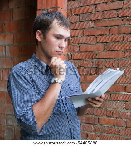a foreman with documents against  the brick wall