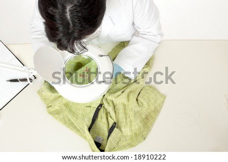 A forensic investigator observes and obtains samples from a shirt for further analysis. - stock photo