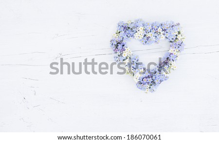 a forget-me-not arrangement in a heart shape on a painted wooden background - stock photo