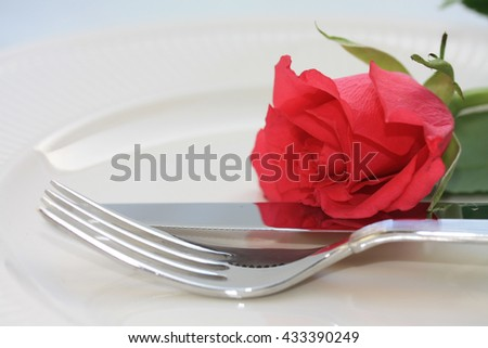 A fork and knife and a red rose, perfect for a dinner invitation