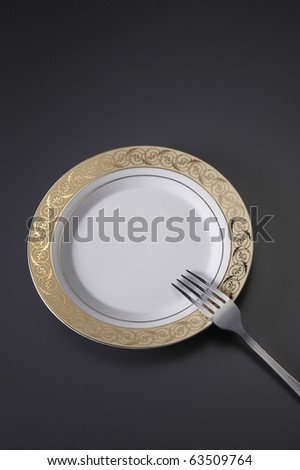 A fork resting on a plate on a dark colour table top. - stock photo