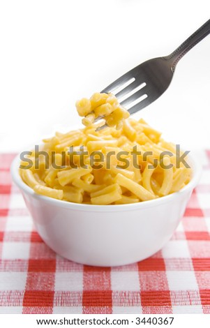 A forkful of macaroni and cheese, in front of a bowl of mac and cheese. On a red checkered placement. Selective focus, on the pasta on the fork. - stock photo
