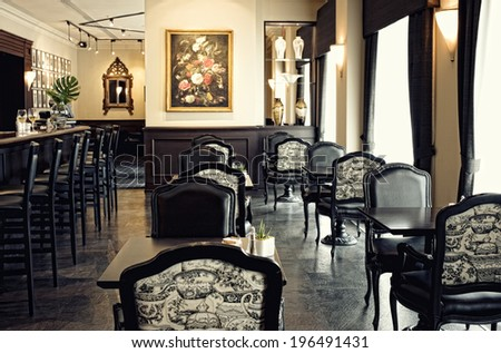 A formal dining area with small tables and stools at a bar.