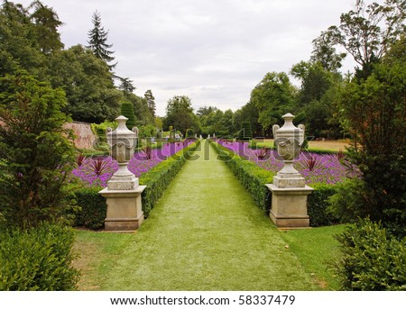 A Formal  English Landscape garden with Box Hedging and Statues on Plinths - stock photo