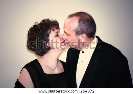 A formally dressed middle aged couple kissing.  Soft lighting effect. - stock photo