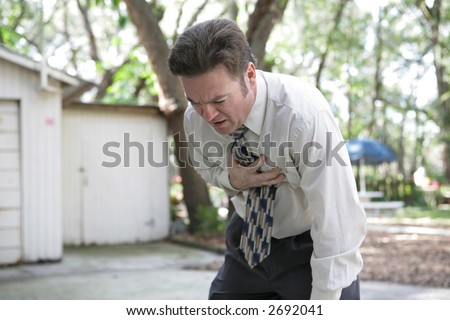 A forty year old man doubled over with chest pain. - stock photo