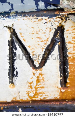 A found letter, part of an entire alphabet, hand painted onto the stern of an old fishing vessel. Suitable for use as part of a headline or as a drop capital at the beginning of a paragraph. - stock photo