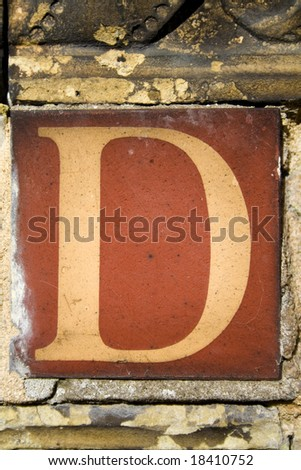 A found letter, part of an entire alphabet, in the form of an antique terracotta tile. Suitable for use as part of a headline or as a drop capital at the beginning of a paragraph. - stock photo