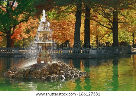 A fountain atop a pile of stones in Tower Grove Park (St. Louis) in front of a background of peak autumn color.
