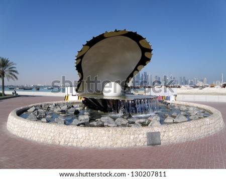 A fountain featuring an oyster with a gigantic pearl inside with the Doha skyline behind it.. - stock photo