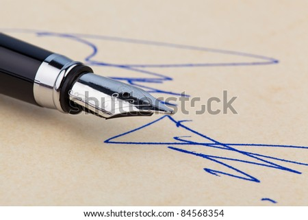a fountain pen and a signature on yellow paper. symbolic of closing deals. - stock photo