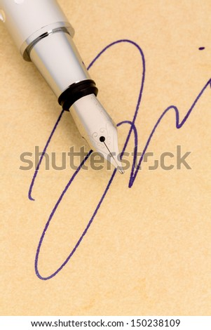 a fountain pen and a signature on yellow paper. symbolic photo for contract, and graphology testament - stock photo
