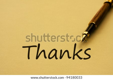 A fountain pen with yellow paper and words thanks, Writing a thank you letter - stock photo