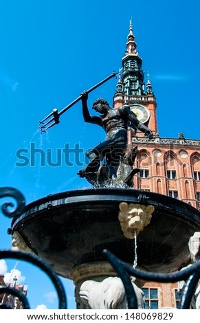 A fountain with a statue of Neptune in the background of the Town Hall. Gdansk. Poland - stock photo