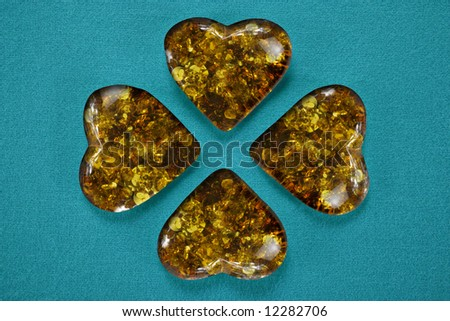 A four leaved clover's shape on velvet background filled with hearts of fossil Amber from Poland, belonging to Oligocene (Cenozoic era)