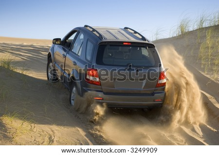 A four-wheel-drive drives through the   sand dunes. - stock photo