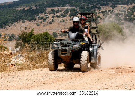 A four-wheeler ATV runs through trail on sunny day - stock photo