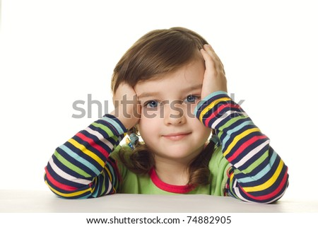 A four year old girl sits at a table - stock photo
