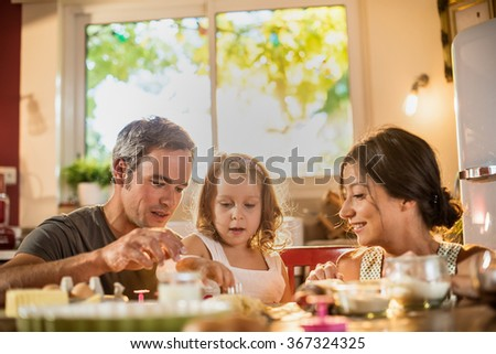 A four years old blonde girl is cooking small cakes with her parents in a luminous kitchen. They are sitting at a wooden table, the little girl is holding  funny smalls baking molds - stock photo