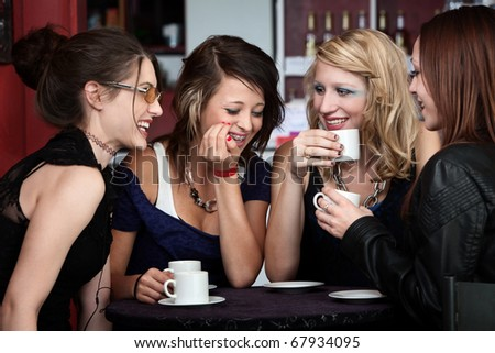 A foursome of pretty girls laughing in a cafe