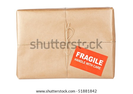 A fragile parcel wrapped in brown paper and tied with rough twine, isolated on white background. Shallow depth of field - stock photo