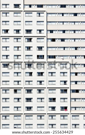 A fragment of a facade of a building, showing lines of windows on each storey of the high rise structure. - stock photo