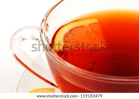 A fragment of a glass cup of tea and a slice of lemon.