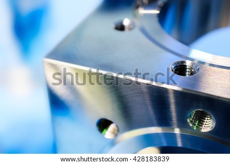 A fragment of a metal cube with holes and metric thread. Fine milling on CNC machine. Shallow depth of field. Toning in the color blue industrial cold. - stock photo