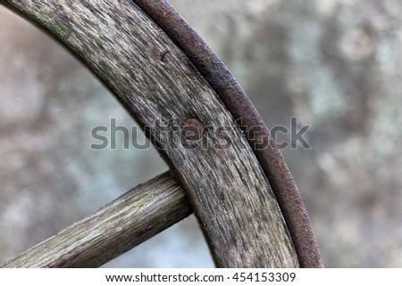 A fragment of a wooden wagon wheel with an iron rim and spokes
