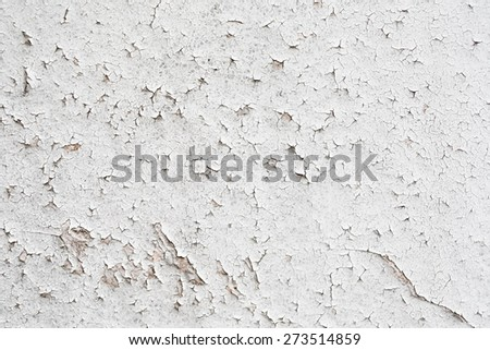 A fragment of the old wall painted with white paint, cracked over time. Peeling paint background. - stock photo