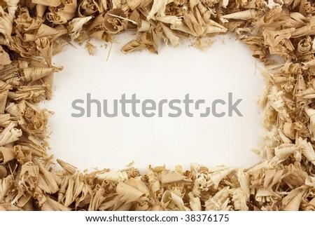 A frame/border of wood shavings around a blank white center - stock photo