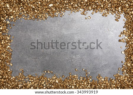A frame of Gold nugget grains, on cement background - stock photo