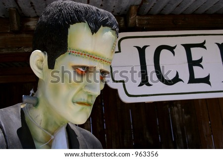 A Frankenstein statue next to an old-fashioned Ice sign.