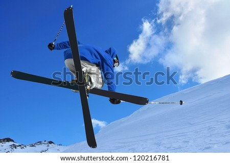 a free style skier performing a high jump. In the background ski lifts in the mountains - stock photo