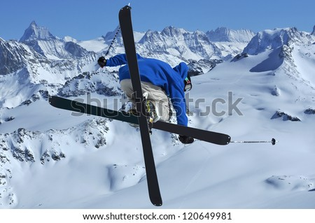 A freestyle skier jumping in the high mountains with crossed skis - stock photo