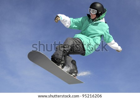a freestyle snowboarder jumping against a blue sky