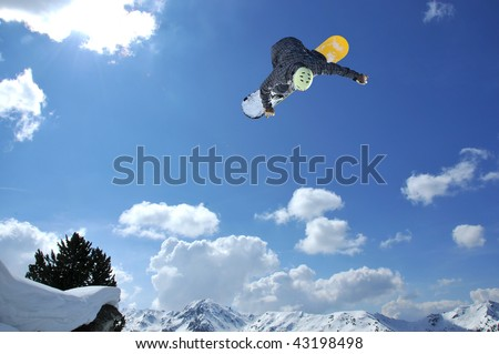 a freestyle snowboarder jumping with the alps in the background