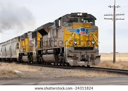 A freight train, needing a wash smokes through the countryside. - stock photo