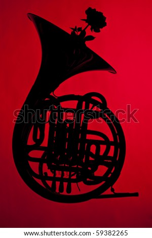 A French horn silhouette with a flower isolated against a red background. - stock photo