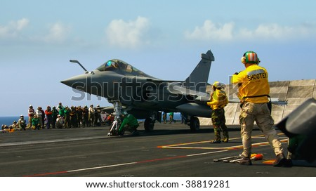 A French rafale fighter prepares to launch from an aircraft carrier in the ocean - stock photo