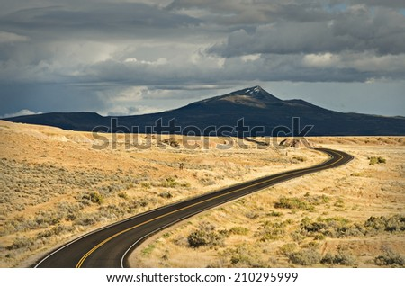 A fresh black-top road stretches over the countryside nearby Craig, Colorado. - stock photo