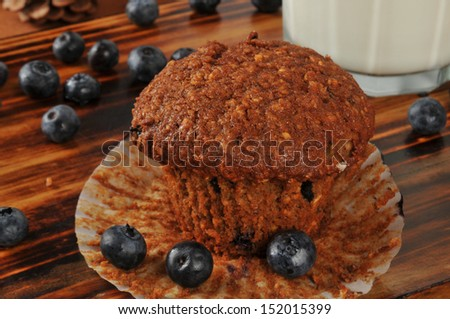 A fresh bran and flaxseed muffin with organic blueberries and milk - stock photo
